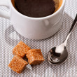 Black sugar spoon and coffee cup on braided rug — Stock Photo