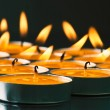 Plate groups candles shine in the darkness — Stock Photo