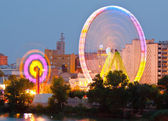 Fair Ferris wheel adorned with lights spinning at dusk — Stock Photo
