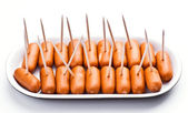Cocktail sausages; punctured tray with chopsticks — Stock Photo
