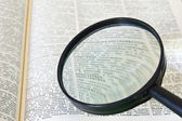 Reading text in book through magnifying glass — Stock Photo