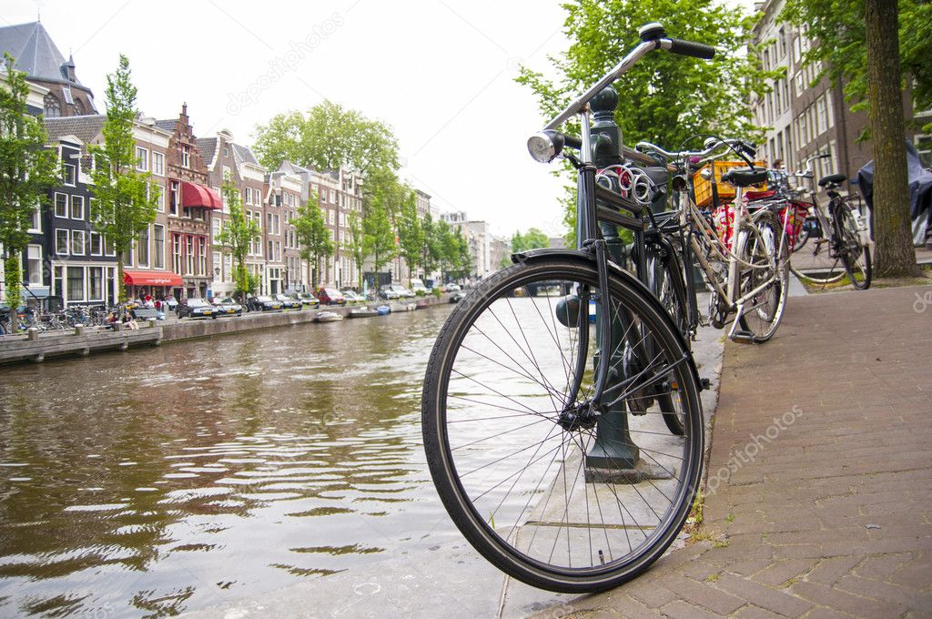 AMSTERDAM, HOLLAND - MAY 29: Detail of bicycle chained by canal in the city centre. May 29, 2012 in Amsterdam. It is estimated that there are about 550 thousand bikes in Amsterdam. — Stock Photo #11227095