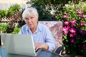 QUizzical Senior Woman with Computer — Stock Photo