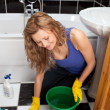 Yound woman sitting on the ground in a bathroom — Stock Photo