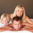 Smiling family having fun together lying on bed — Stock Photo #10820517
