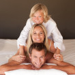 Happy family having fun together lying on bed — Stock Photo