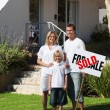 Happy family in front of their new house — Foto Stock