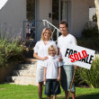 Happy family in front of their new house — Stockfoto