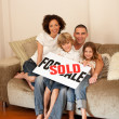 Young family sitting on the sofa with a plakat — Stock Photo