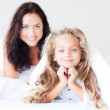 Young Mother and her daughter on bed — Stock Photo #10820733