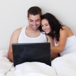 Animated couple using a laptop at home — Stock Photo #10820849