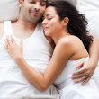 Young woman lying in bed with a boy — Stock Photo #10820895