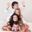Family having fun in bed with hands up — Stock Photo