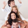 Smiling family climbing on top of each other — Stock Photo