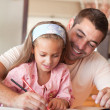 Concentrated girl painting with her father — Stock Photo