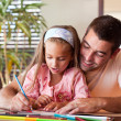 Stock Photo: Amazed little girl drawing with her smiling father
