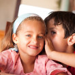Stock Photo: Boy whisper in ear of his sister