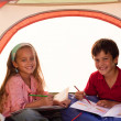 Stock Photo: Smiling siblings in tent