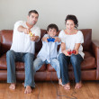 Young family on sofa playing video games — Stock Photo