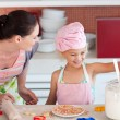 Merry little girl baking with her mother cookies — Stock Photo #10821239