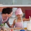 Young mother in kitchen teaching child - Stock Photo