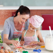 Sweet little girl showing her mother her cookies - Stock Photo