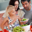 Cute girl with her parents in the kitchen — Stock Photo