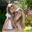 Beautiful mother and daughter outdoors in the sunshine - Stock Photo