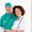Surgeon and nurse smiling at the camera — Stock Photo