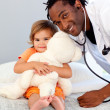 Stock Photo: Caring young doctor with cute girl