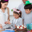 Stock Photo: Cute girl unpacking Birthday presents with her family