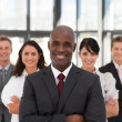 Smiling confident business team looking at the camera - Stock Photo