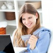 Happy woman with a credit card and a laptop — Stock Photo