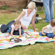 Stock Photo: Mother and daughters having picnic together