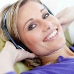 Charming woman lying down on sofa listening music — Stock Photo