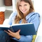 读一本书在客厅里的幸福女人 — 图库照片