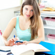 Stock Photo: Smiling female teenager studying in kitchen