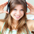 Stock Photo: Positive woman listening to music with headphones