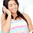 Stock Photo: Radiant young woman sitting on sofa and listening music