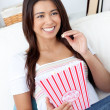 Woman sitting on sofa and eating popcorn — Stock Photo