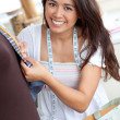 Stock Photo: Delighted young woman working in a store
