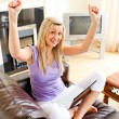 Cheering woman sitting on sofa and working — Stock Photo #10824110