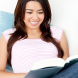 Portrait of a smiling woman reading a book — Stock Photo