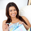 Glowing woman opening a present sitting on a sofa — Stock Photo