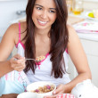 Smiling woman eating muesli with fruits — Stock Photo #10824316