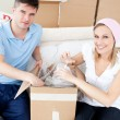 Smiling young couple unpacking boxes with glasses — Stock Photo