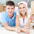 Jolly couple lying between boxes — Stock Photo #10824569