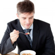Young businessman using a laptop while having breakfast — Stock Photo
