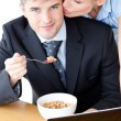 Smiling businessman eating breakfast while wife kissing his chee — Stock Photo