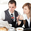 Stock Photo: Young couple of business reading newspaper while having